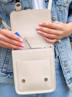 Vrouw die handdesinfecterend middel in haar beurs zet