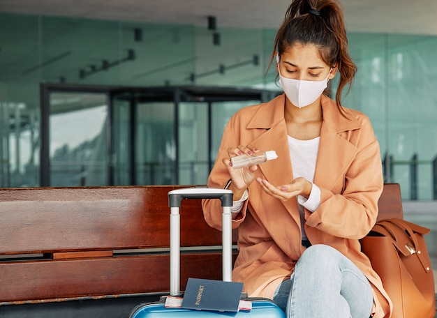 Vrouw die handdesinfecterend middel op de luchthaven gebruikt tijdens pandemie