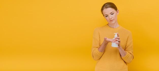 Vrouw die handdesinfecterende vloeistof of zeep bij de hand gebruikt