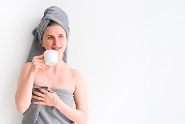 Vrouw die handdoeken draagt en van een kop drinkt