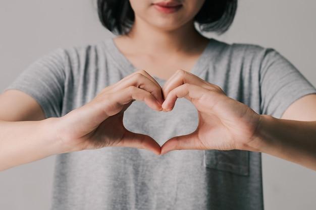 Vrouw die handen in hartvorm, donatie, gelukkige liefdadigheidsvrijwilliger, wereldhartdagconcept maakt