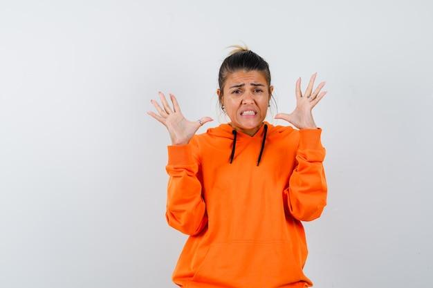 Vrouw die handen op een agressieve manier opsteekt in oranje hoodie en er walgelijk uitziet