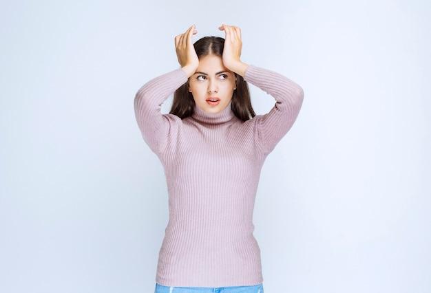 Vrouw die handen op haar hoofd legt en er verward uitziet.