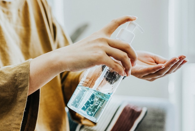 Vrouw die handen schoonmaakt met een handdesinfecterende gel om besmetting met coronavirus te voorkomen prevent