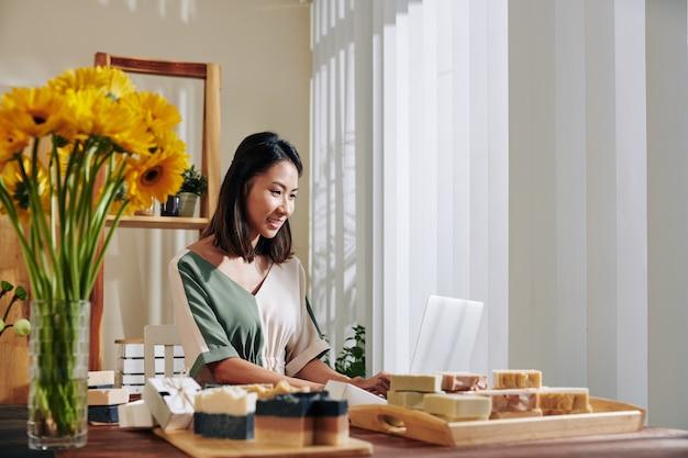 Vrouw die handgemaakte zeep online verkoopt