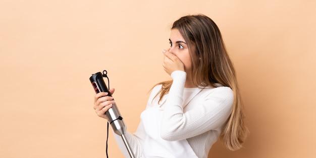 Vrouw die handmixer over geïsoleerde achtergrond gebruikt die mond behandelt en aan de kant kijkt