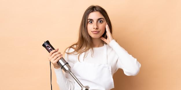 Vrouw die handmixer over geïsoleerde gefrustreerde muur gebruikt en oren behandelt