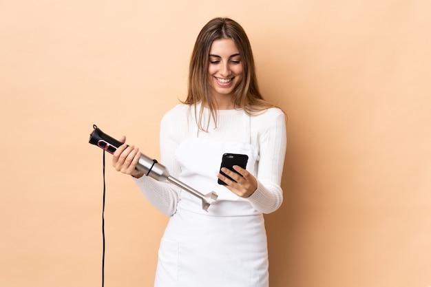 Vrouw die handmixer over geïsoleerde muur gebruikt die een bericht met mobiel verzendt