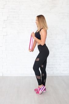 Vrouw die handoefeningen doet die elastiekje voor sporten gebruikt