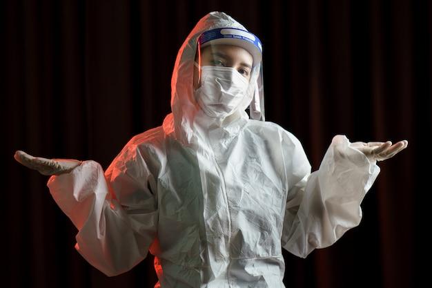 Vrouw die handschoenen, biohazard beschermend pak, gelaatsscherm en masker draagt. voor coronavirus of covid-19-bescherming.