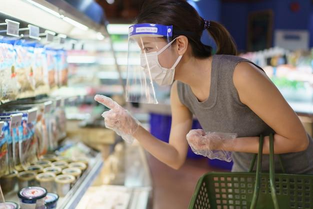 Vrouw die handschoenen, gezichtsschild en masker draagt dat groenten kiest. paniek winkelen tijdens de pandemie van het coronavirus.