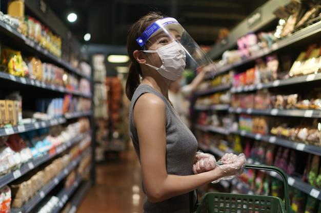 Vrouw die handschoenen, gezichtsschild en masker draagt. paniek winkelen tijdens de pandemie van het coronavirus.