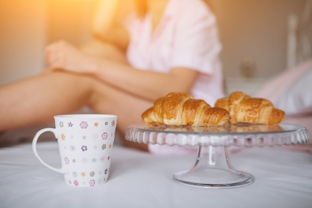 Vrouw die heerlijk croissant met koffie in bed eet