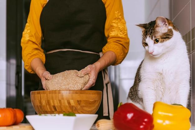 Vrouw die heerlijke pizza bereidt met haar lieve kat. zelfgemaakt concept.