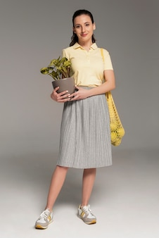 Vrouw die herbruikbare schildpadzak draagt en bloempot vasthoudt