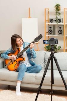 Vrouw die hercodeert terwijl het spelen van gitaar