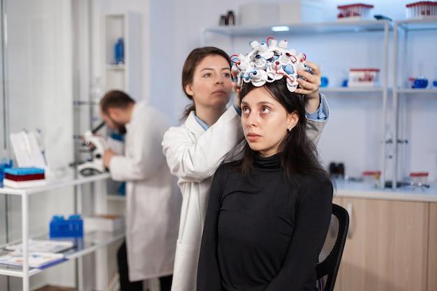 Vrouw die hersengolfheadset draagt in modern medicijnlaboratorium met neuroloog arts gezondheidsarts. neurowetenschappelijke dokter die sensoren op de patiënt zet. het vinden van genezing voor ziekte.