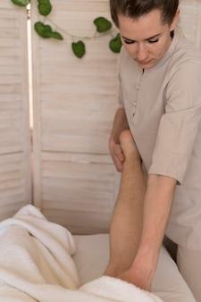Vrouw die het been van de cliënt masseert