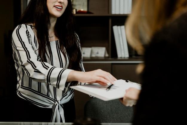 Vrouw die het contract overhandigt aan de klant
