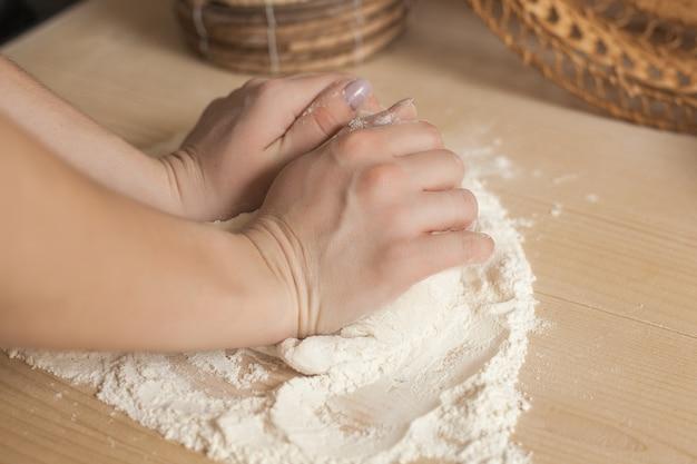 Vrouw die het deeg voorbereidt. close-up nog van vrouwen` s handen met dochter en bloem. italiaans bereidingsproces.