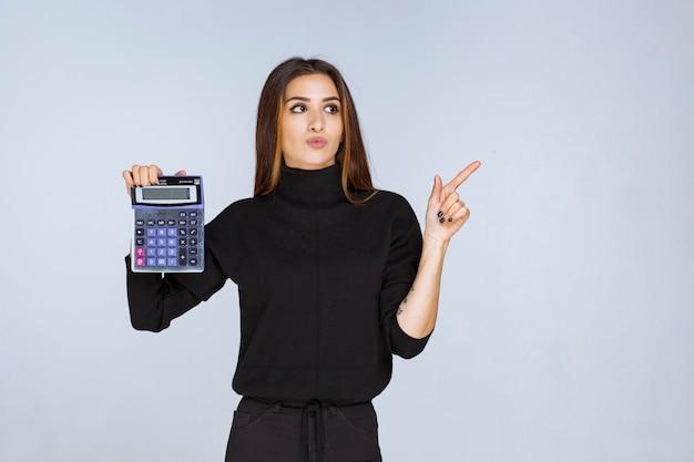 Vrouw die het eindresultaat op de rekenmachine laat zien.