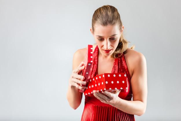Vrouw die het geschenk opent en is blij