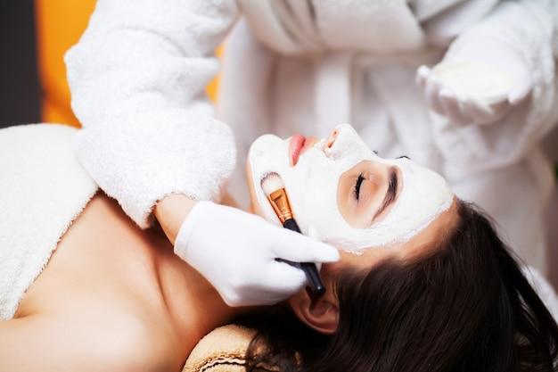 Vrouw die het gezichtsmasker van het kuuroord in schoonheidscentrum krijgt