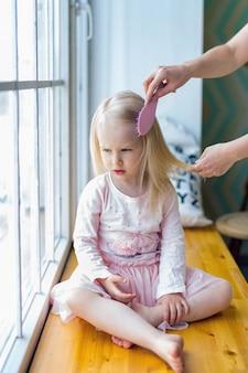 Vrouw die het haar van het jonge meisje borstelen terwijl het zitten dichtbij venster. vrouw die het haar van haar 3-jarige dochter kamt