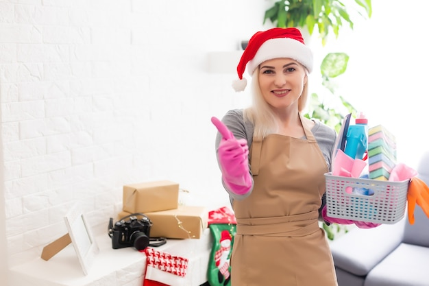 Vrouw die het huis schoonmaakt. grappig meisje in santa helper hoed. kersttijd en huishoudelijk werk concept.