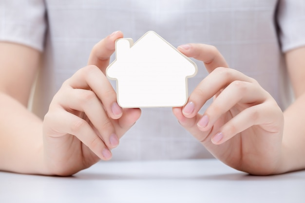 Vrouw die het kleine huis houdt. concept voor onroerend goed bedrijf.
