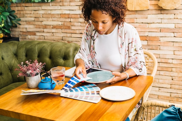 Vrouw die het kleurenmonster met plaat op lijst aanpast
