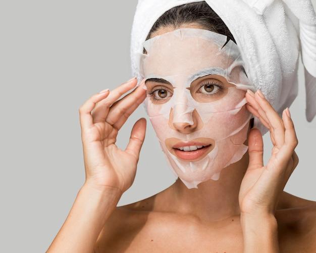 Vrouw die het masker van de gezichtsschoonheid toepast