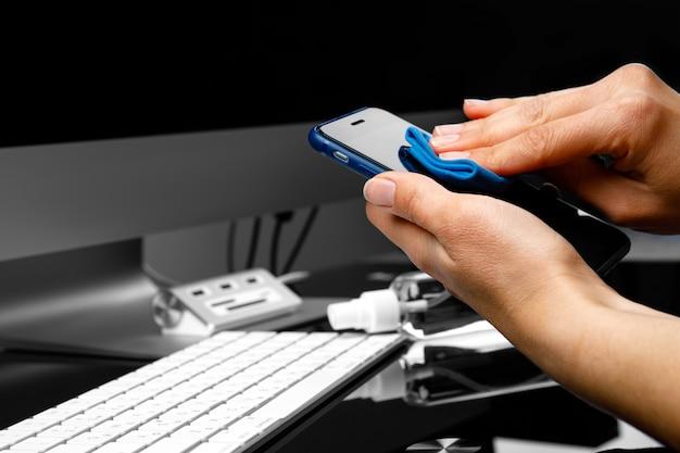 Vrouw die het mobiele telefoonscherm met desinfecterend middel afvegen
