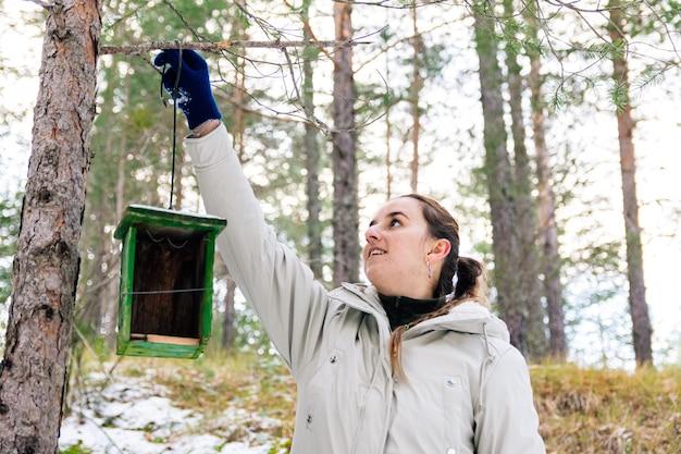 Vrouw die het nest van een houten vogel in het bos plaatst. besneeuwde landschap