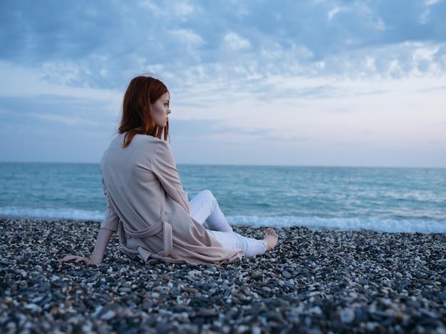 Vrouw die het oceaanlandschap bewondert, ontspanningsavond natuur