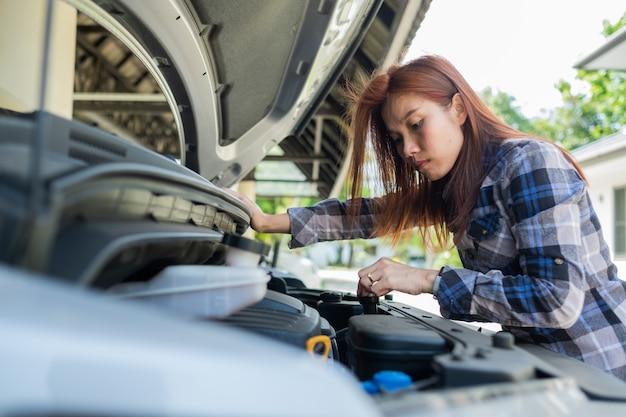 Vrouw die het oliepeil in een auto controleert