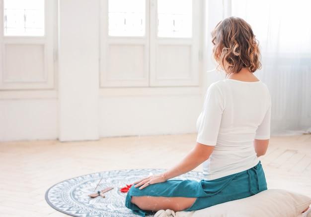 Vrouw die het praktizeren yoga voor kaarsen en rode roze bloemblaadjes, mening van rug mediteren