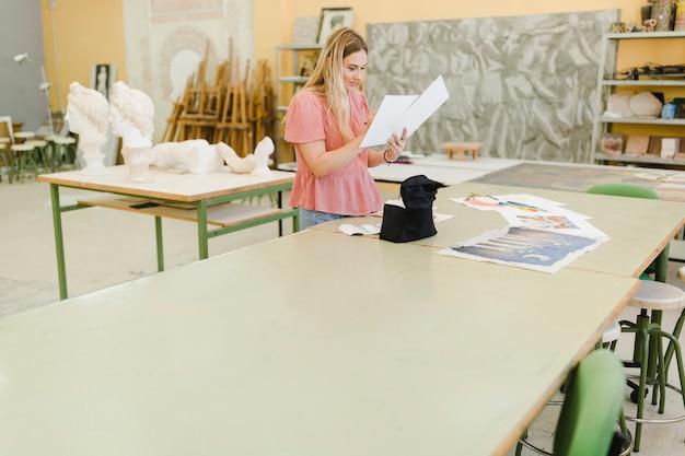 Vrouw die het schilderen in de workshop bekijkt