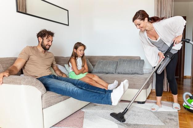 Vrouw die het tapijt stofzuigt