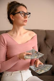 Vrouw die het zwarte glazen denken aan geld draagt
