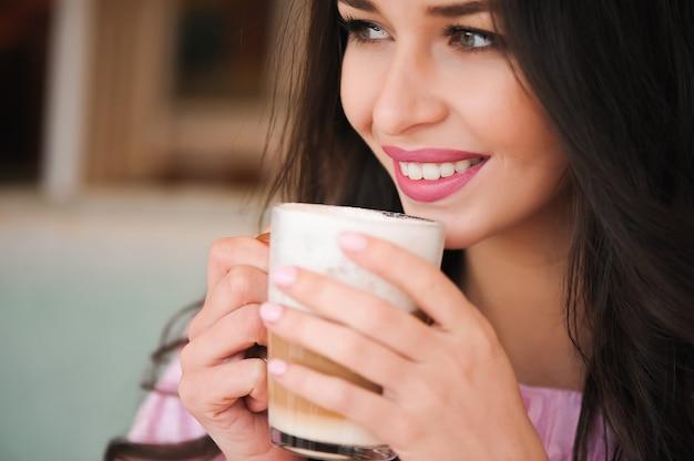 Vrouw die hete cappuccinokoffie drinkt en cake eet in een koffie.