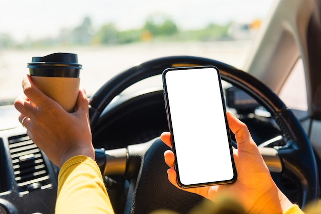 Vrouw die hete koffie afhaalmaaltijden drinkt in de auto en het lege scherm van de smartphone gebruikt
