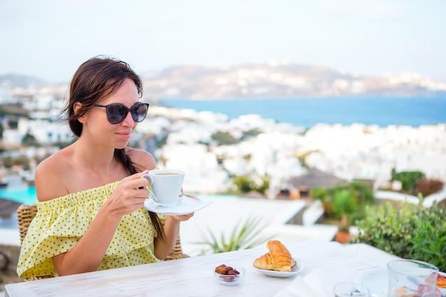 Vrouw die hete koffie op het terras van het luxehotel drinkt met overzeese mening bij toevluchtrestaurant.