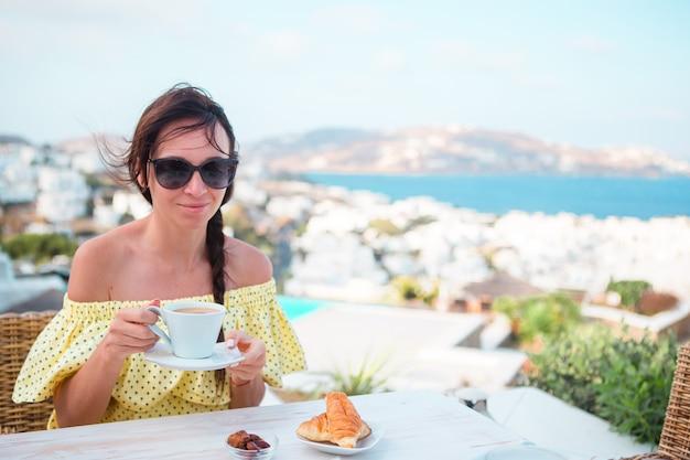 Vrouw die hete koffie op het terras van het luxehotel met overzeese mening drinken bij toevluchtrestaurant.