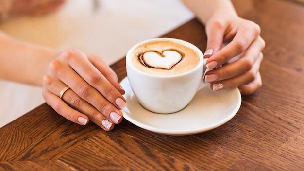 Vrouw die hete kop van koffie, met hartvorm houdt