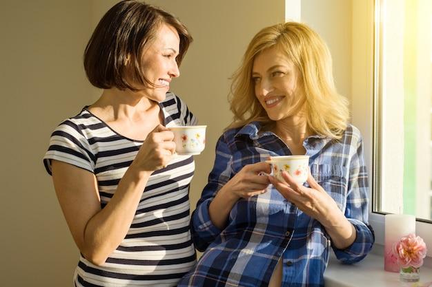 Vrouw die hete koppen van koffie het drinken houdt,