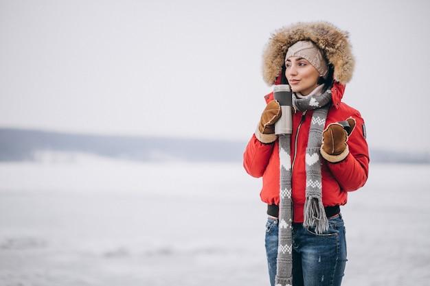 Vrouw die hete thee in de winter buiten drinkt