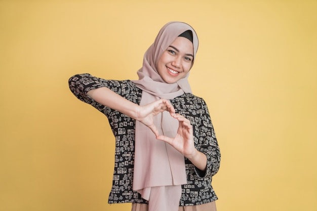 Vrouw die hijab draagt, gebaart een hart met vingers