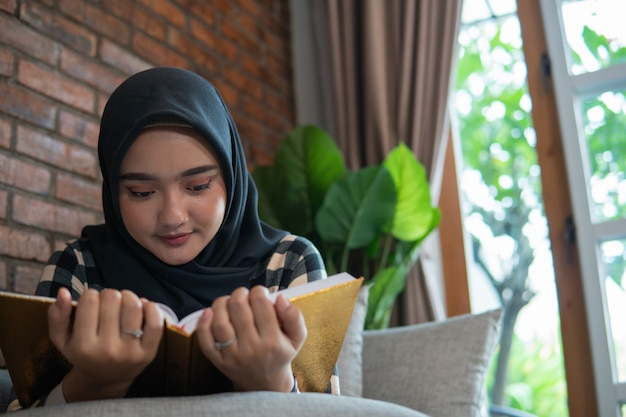 Vrouw die hijab lezing quran draagt