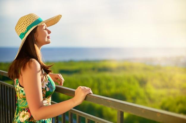 Vrouw die hoed draagt die aan het overzees kijkt